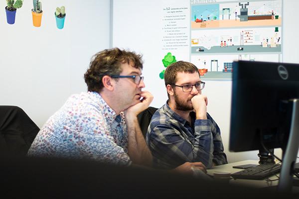 Collega's overleggen op kantoor achter laptop